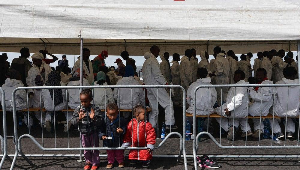 Inmigrantes bajo una carpa de Cruz Roja tras llegar a Salerno, Italia