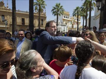 El presidente del Gobierno y del Partido Popular, Mariano Rajoy (c), saluda a varios vecinos de La Palma del Condado (Huelva),