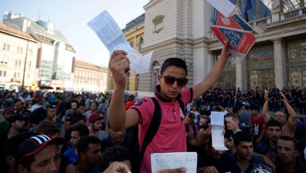 Inmigrantes muestran sus billetes de tren a las puertas de la estación de Keleti