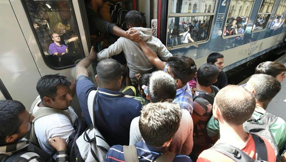 Inmigrantes subiendo a un tren en Hungría
