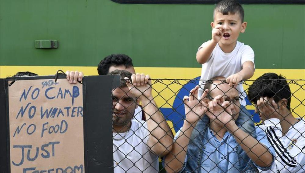 Refugiados resisten junto al tren que permanece varado hoy en la estación ferroviaria de Bicske