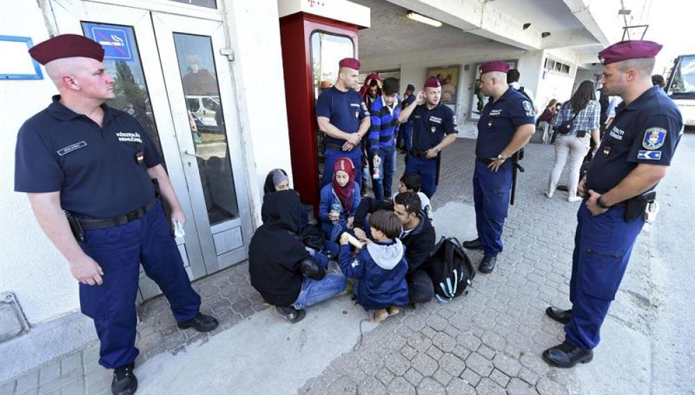 Policías observan a un grupo de refugiados durante el reparto de alimentos