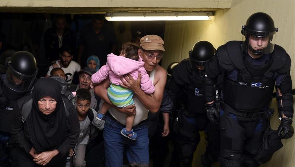 Varios inmigrantes, acompañados por policías,