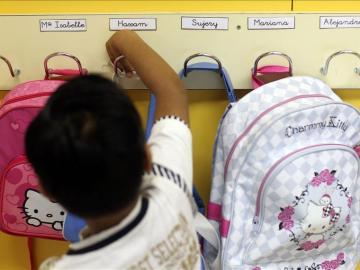 Un alumno coloca su mochila en su colegio