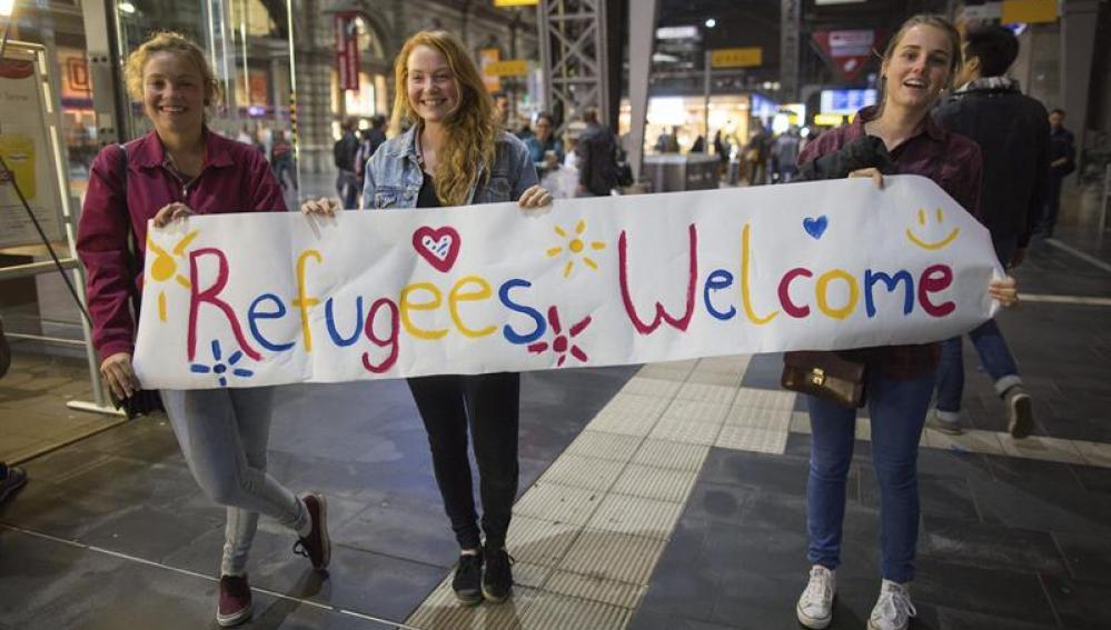 Tres voluntarias alemanas esperan con un cartel de bienvenida a los refugiados