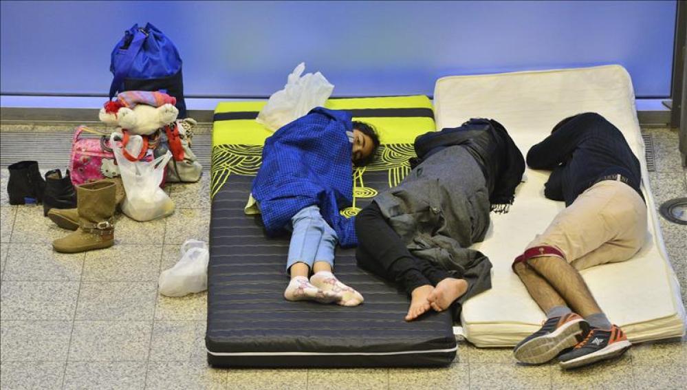 Una familia de refugiados descansa sobre dos colchones en el recinto ferial de Messe Erfurt