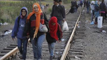 Inmigrantes caminan junto a una línea de tren cerca de la frontera húngara