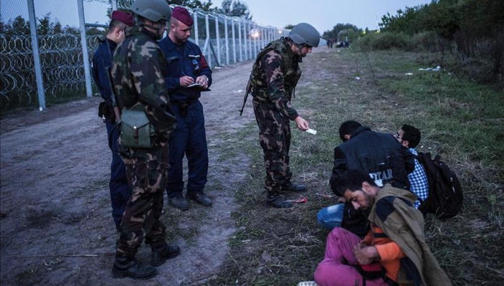 Policías y soldados comprueban la documentación de varios refugiados en la frontera entre Serbia y Hungría