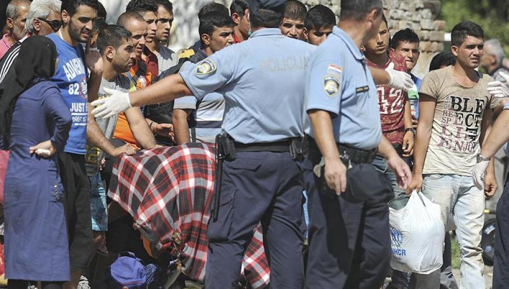 Policías croatas dirigen a varios refugiados