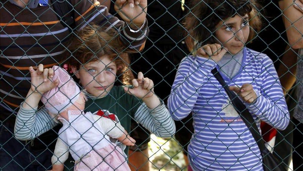 Dos niños refugiados esperan este jueves para registrarse tras haber cruzado la frontera entre Serbia y Croacia