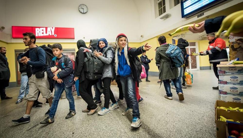 Un grupo de refugiados recibe alimentos