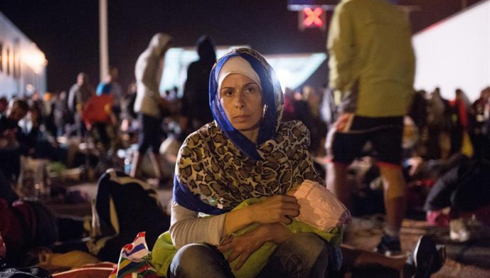 Una mujer junto a su bebé en la frontera entre Croacia y Eslovenia