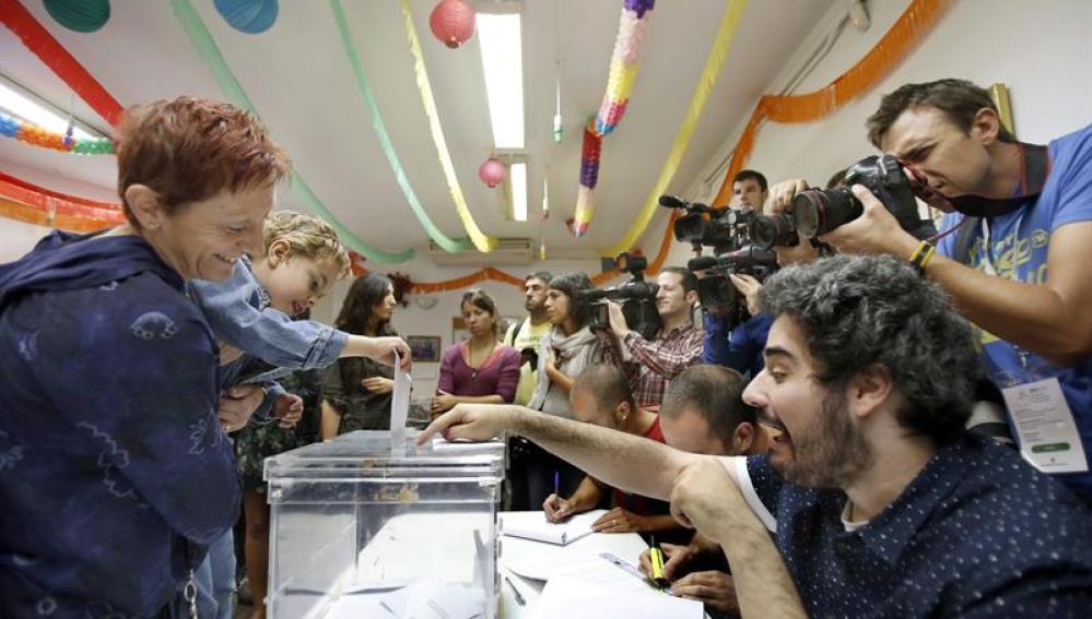 Un niño, en brazos de su madre, deposita el voto en la urna