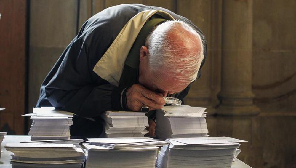 Una persoma observa con una lupa las papeletas de los diferentes partidos del 27S