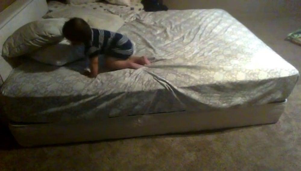 Un bebé a punto de descender de una cama