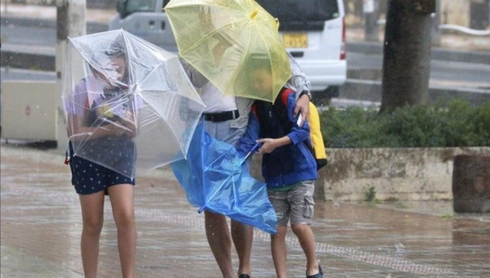 Varios viandantes luchan contra los fuertes vientos y la lluvia