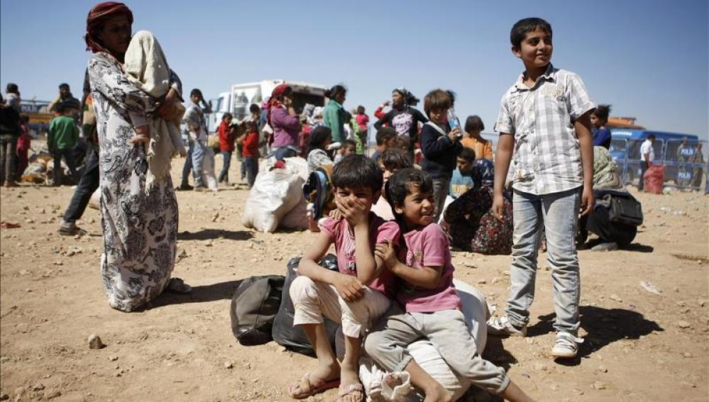 Niños refugiados junto a adultos (Archivo)