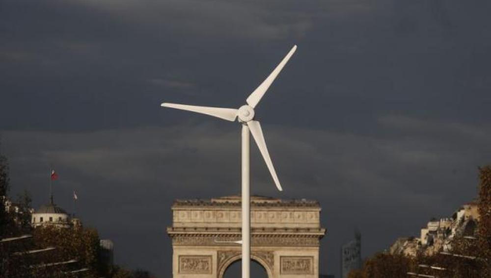 Un molino de energía eólica delante del Arco de Triunfo