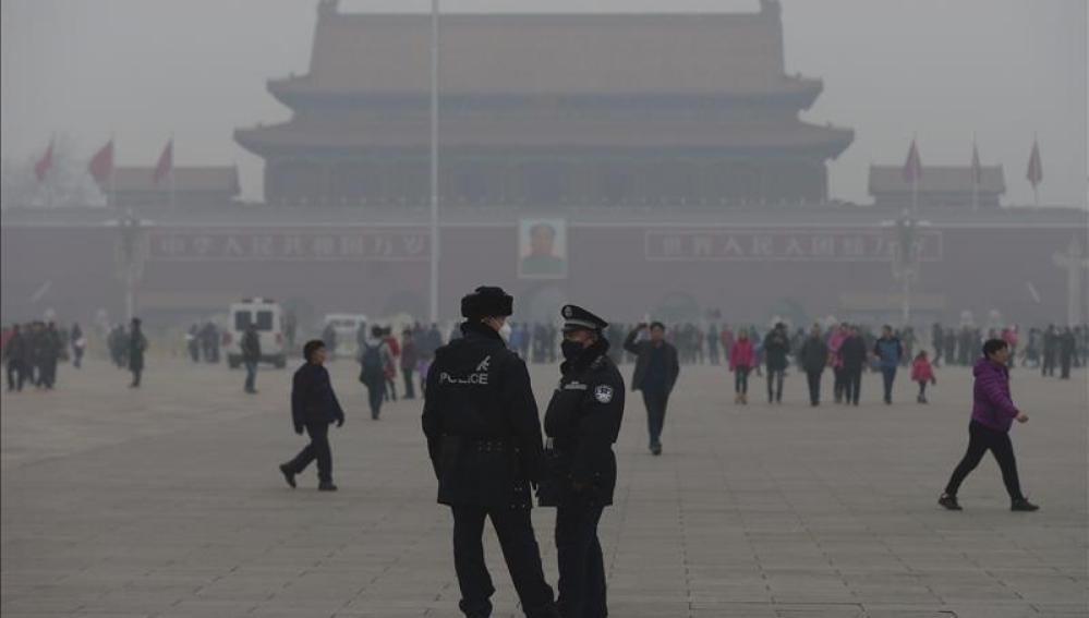 Dos policías usan mascarillas mientras hacen guardia en la plaza de Tiananmen en Pekín