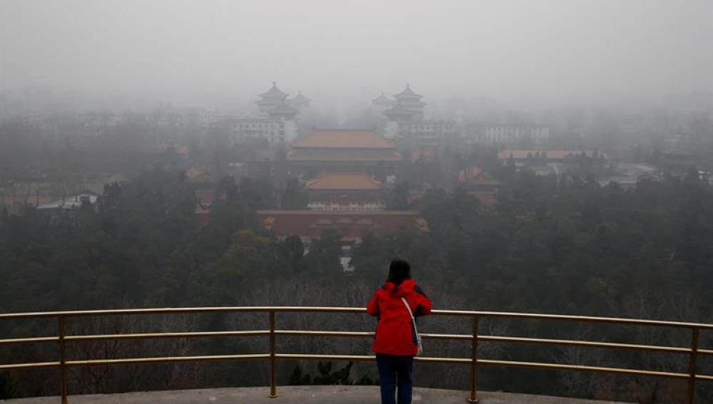 Una mujer observa el paisaje envuelto por una espesa niebla en Pekín