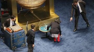 Los niños de San Ildefonso recogen una bola premiada con mil euros que se había caído al suelo, durante el sorteo de Lotería de Navidad
