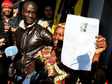 Una mujer feliz muestra una copia del número 79.140, agraciado con el Gordo