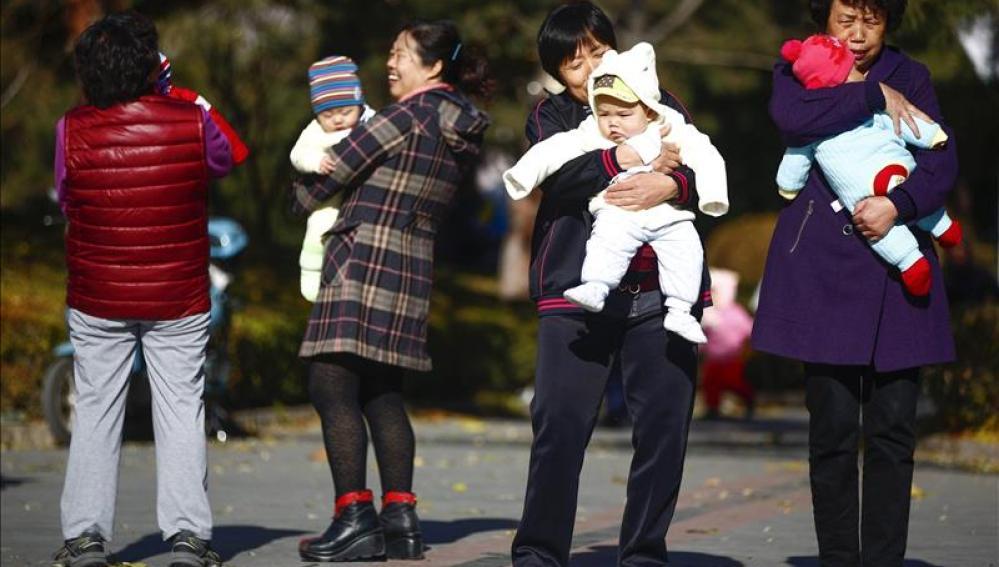 Varias mujeres sujetan en brazos a bebés en un parque de Pekín, China