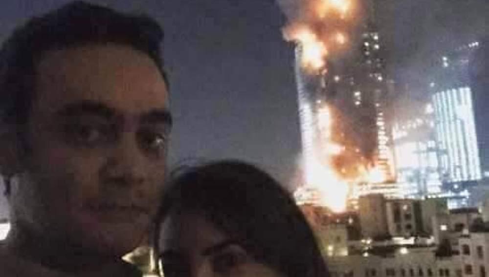 Una pareja se hace un selfie con un edificio en llamas