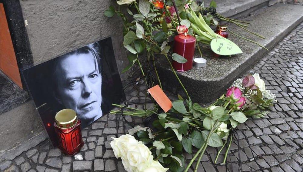 Flores y velas junto a una foto el cantante británico David Bowie