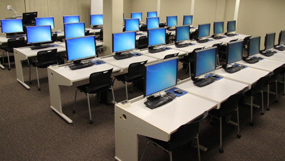 Ordenadores encendidos en un aula vacía