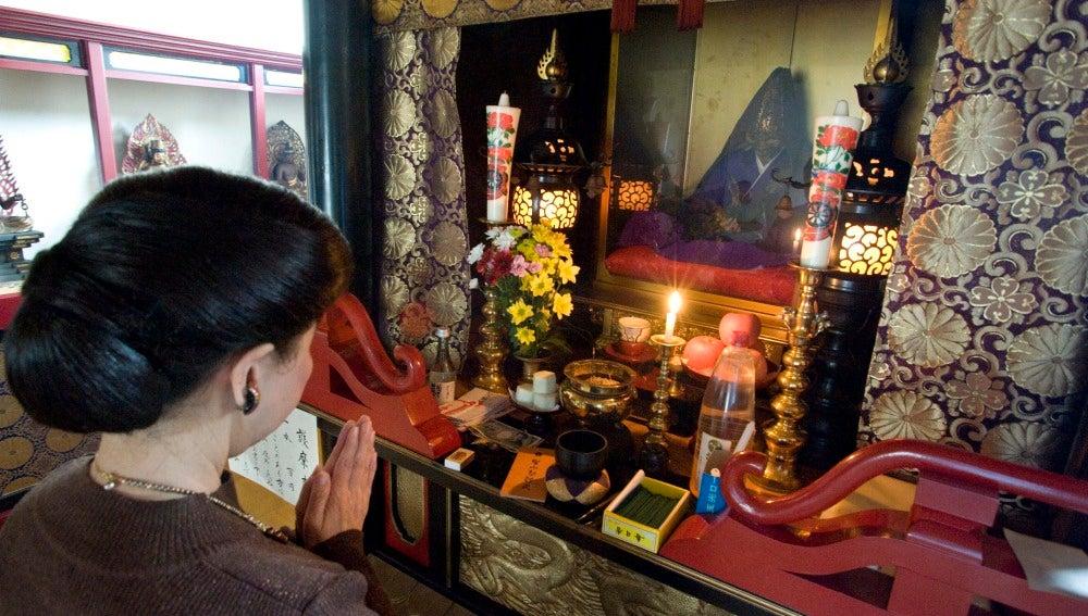Imagen que muestra a una mujer que reza delante de un buda viviente