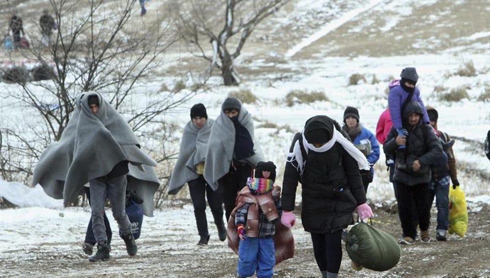 Refugiados de Siria, Irak y Afganistán caminan hacia un campamento temporal en Serbia