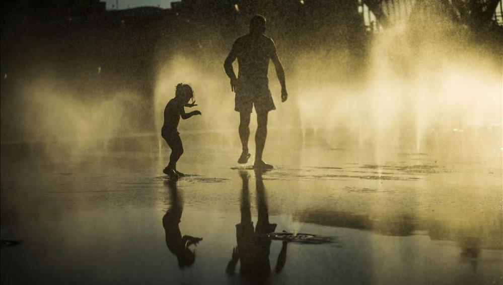 Un padre y su hijo jugando en una fuente