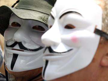 Dos personas con las caretas características de Anonymous