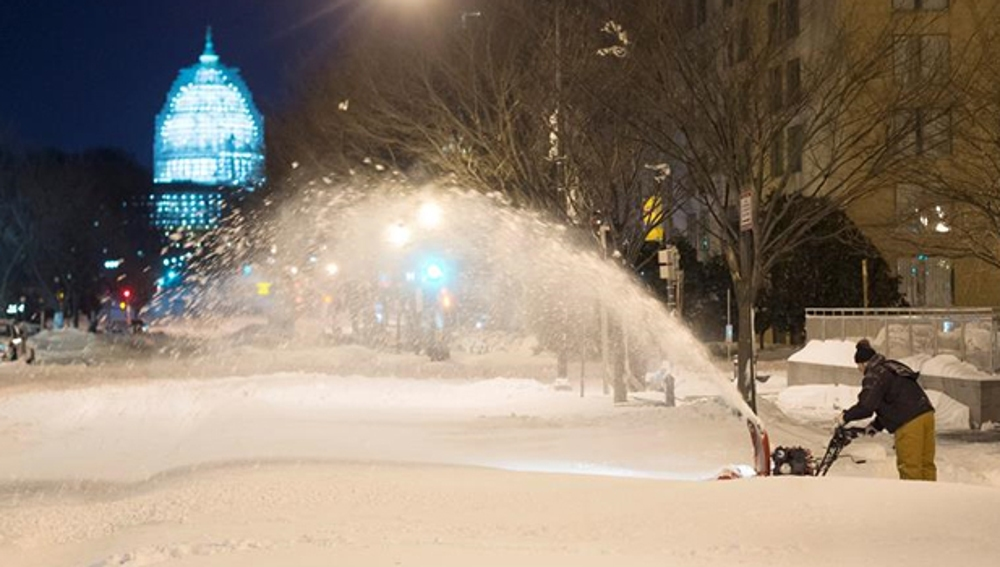 Un trabajador quita nieve con el Capitolio al fondo