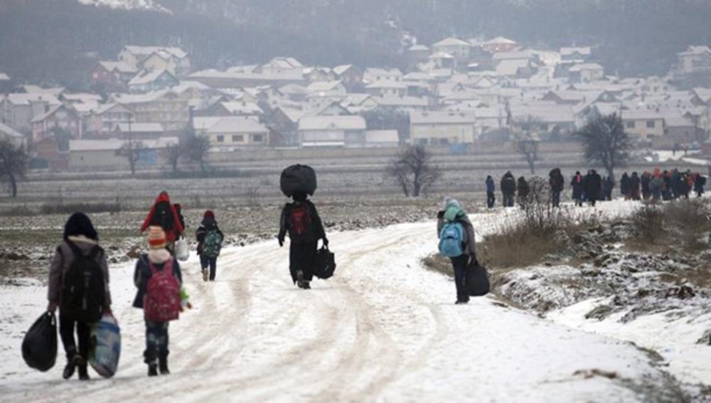 Un grupo de refugiados avanzando por un camino nevado