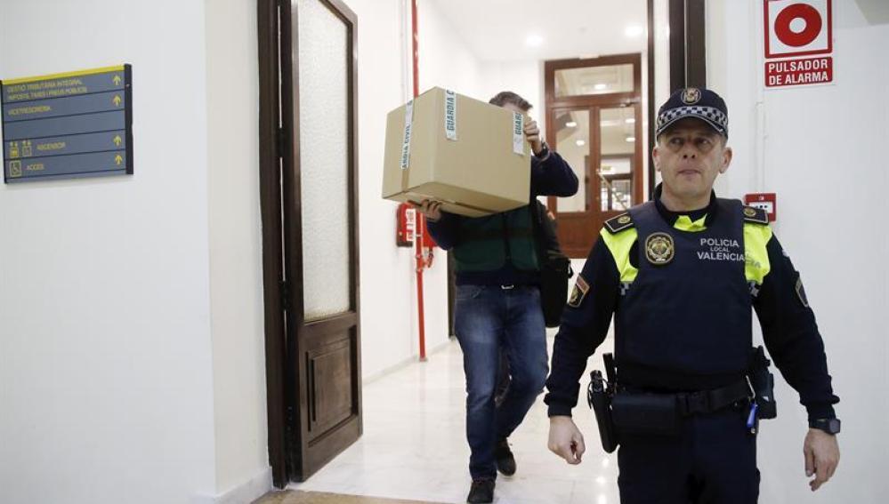 Un agente retira material requisado de las oficinas del PP en Valencia