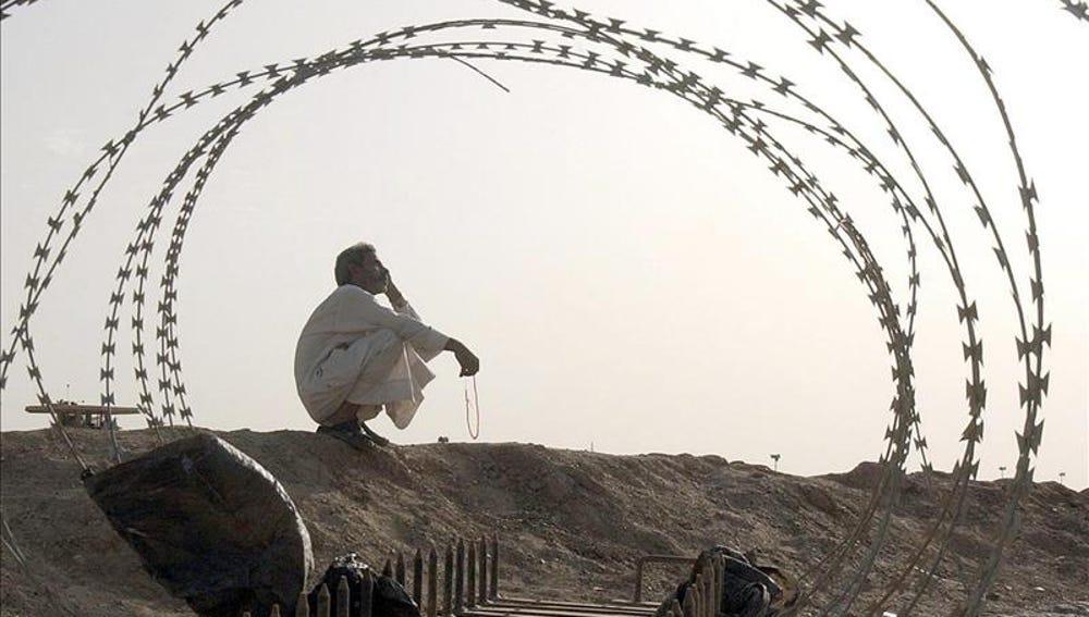 Un iraquí sentado al frente de la prisión de Abu Ghraib al oeste de Bagdad, Irak