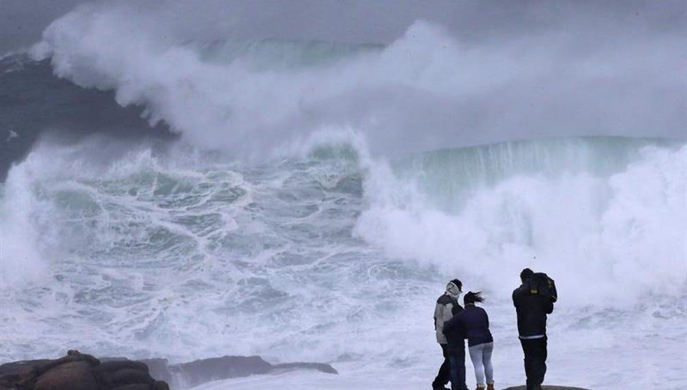 Varios turistas observan las olas en la costa esta tarde en Muxía