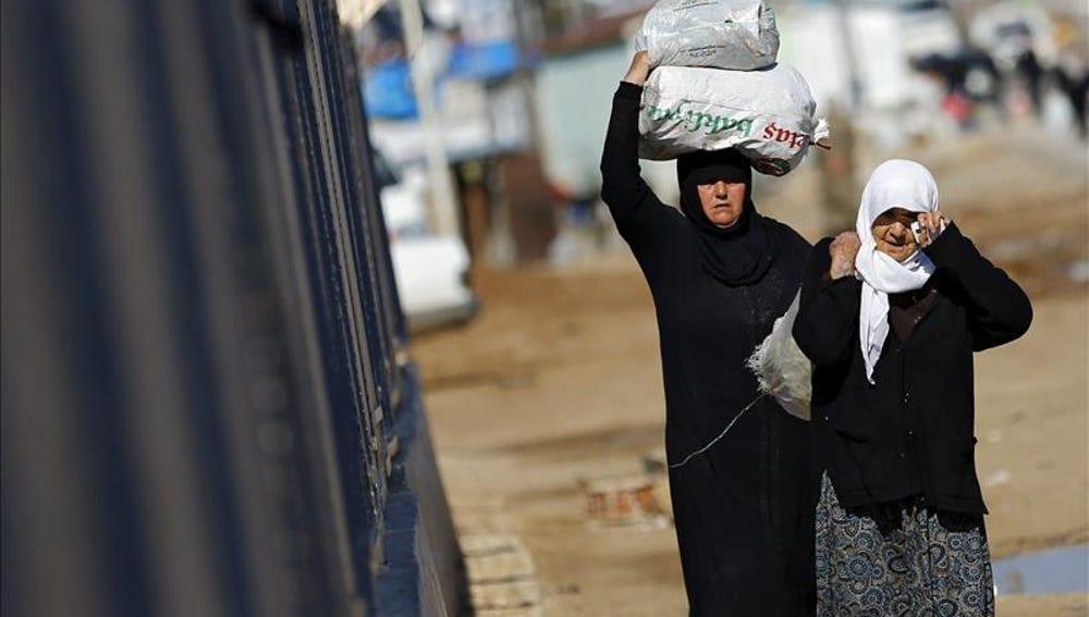 Refugiados sirios trasladan bolsas de alimentos en el paso fronterizo de Öncüpinar, en Kilis,