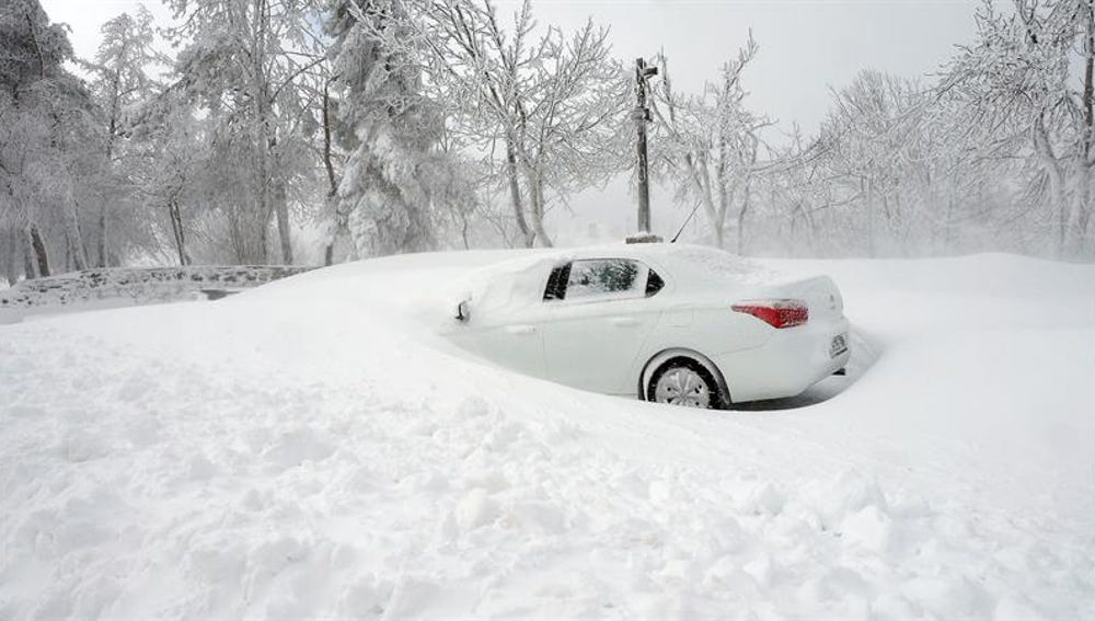 En la foto un coche parcialmente sepultado por la nieve en O Cebreiro.