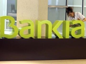 Una operaria limpia el logo de Bankia