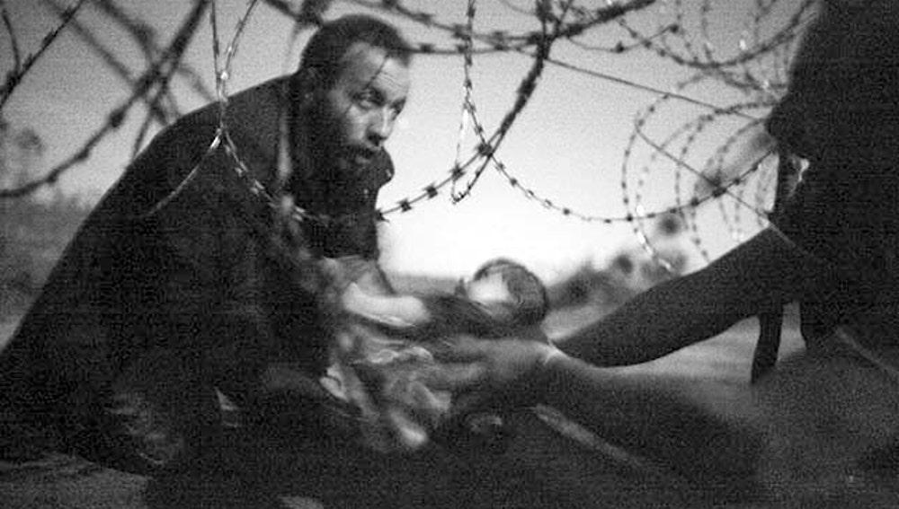 Unos refugiados pasan a un bebé por la frontera entre Serbia y Hungría