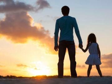 Un padre con su hija durante la puesta de sol