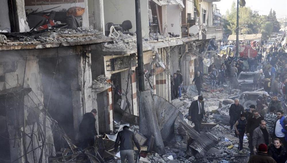 Policías sirios inspeccionan el lugar donde se ha producido un atentado en Homs, Siria