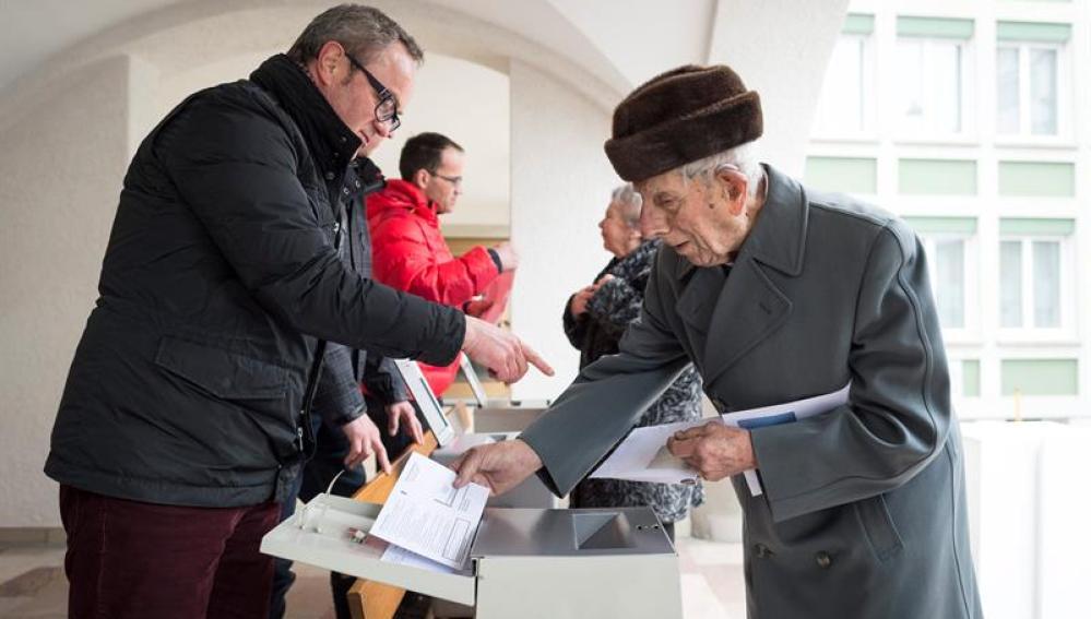 Un hombre deposita su voto en una oficina electoral en Appenzell, Suiza.