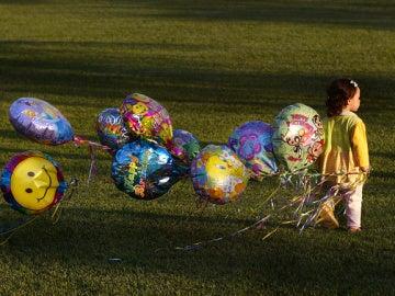 Una niña con globos de helio