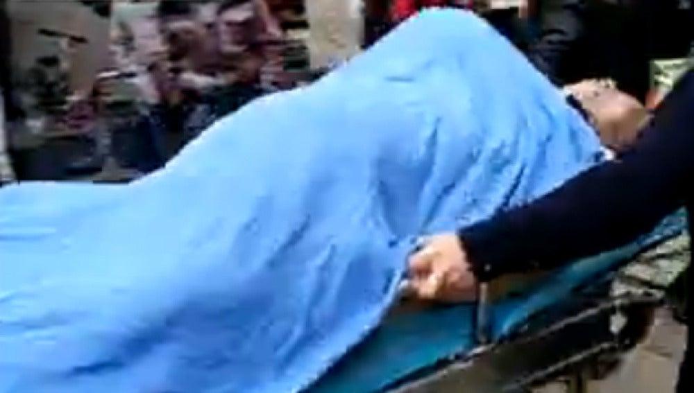 Imagen del fallecido en camilla con la mujer encima tapada por una sabana
