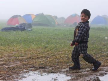 Un niño camina por el campo de refugiados cerca de Idomeni