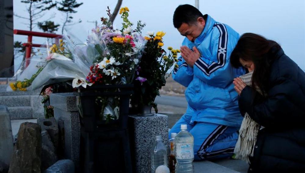 Una pareja reza ante un altar en memoria de las víctimas del terremoto y posterior tsunami